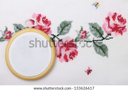 background with embroidered cross on canvas patterns of flowers roses - stock photo