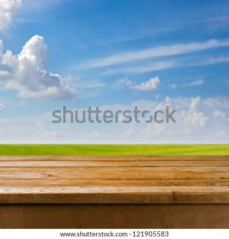 Background with empty wooden table over beautiful meadow - stock photo