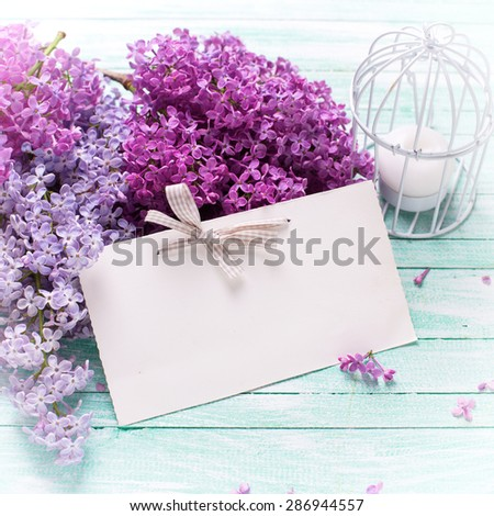 Background  with fresh lilac flowers,  candle and empty tag on turquoise painted wooden planks. Selective focus. Place for text. Square image. - stock photo
