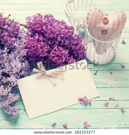 Background  with fresh lilac flowers,  textile decorative heart  and empty tag on turquoise painted wooden planks. Selective focus. Place for text. Square image.  - stock photo