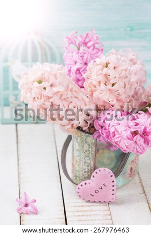 Background with fresh pink hyacinths in vase, little pink heart in ray of light  on white wooden planks against turquoise wall. Selective focus.  - stock photo