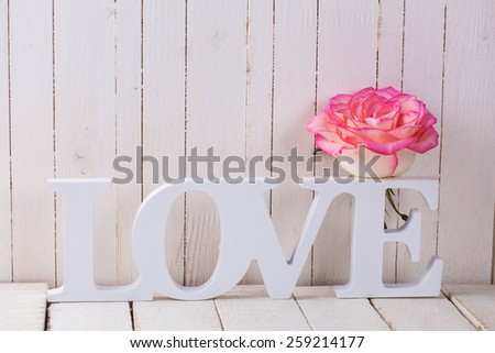 Background with fresh rose and word love.  Rose on white wooden table. Selective focus. - stock photo