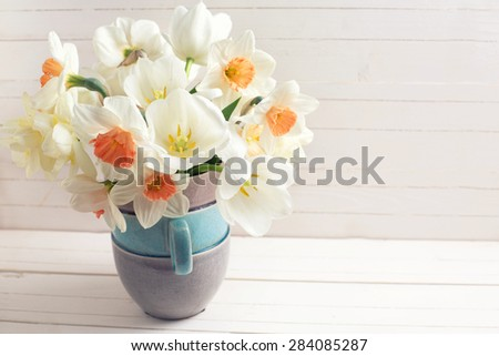 Background with fresh spring  pink daffodils  and white tulips flowers in vase  on white wooden planks. Selective focus. Place for text. Toned image. - stock photo