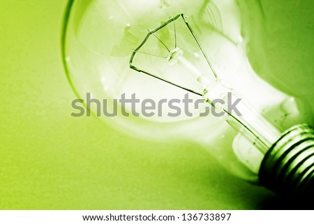 Background with lit lightbulb. Isolated on green - stock photo