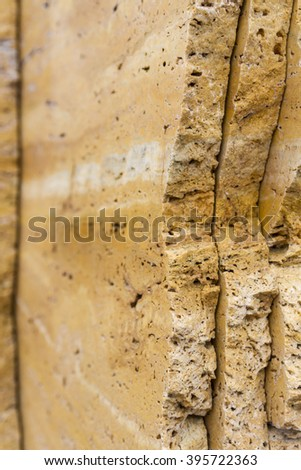 Background with natural stone texture travertine. Travertine warm beige color with pronounced a striped and does not uniform pattern. Banded texture reminiscent of wood pattern. Building material. - stock photo