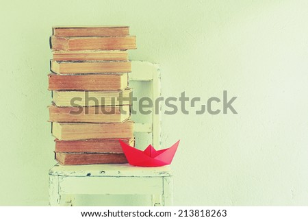 Background with old books, chair and red paper boat - stock photo
