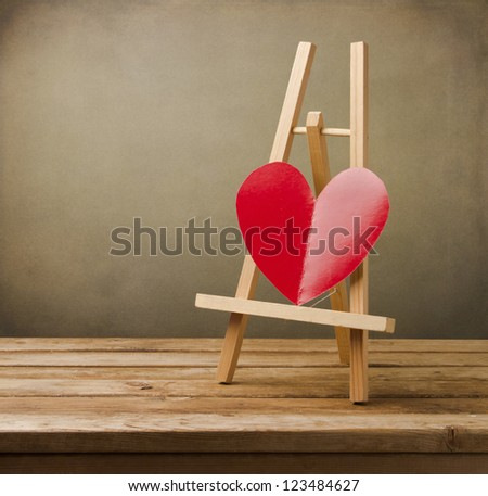 Background with paper heart standing on easel - stock photo