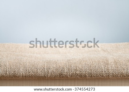 Background with sack cloth on wooden deck table use for product display - stock photo