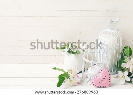Background  with tender apple blossom, candles in decorative bird cages and little pink heart on white painted wooden planks. Selective focus. Toned image.  - stock photo