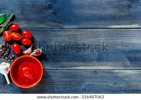 Background with tomato sauce ingredients (cherry tomatoes, fresh herbs, garlic, pepper) over dark wooden board. Food or cooking concept, top view, free text space. - stock photo