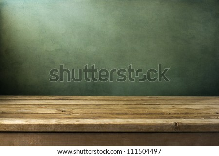 Background with wooden deck table on green grunge background - stock photo