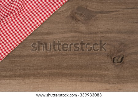 Background with wooden tabletop and checked tablecloth - stock photo