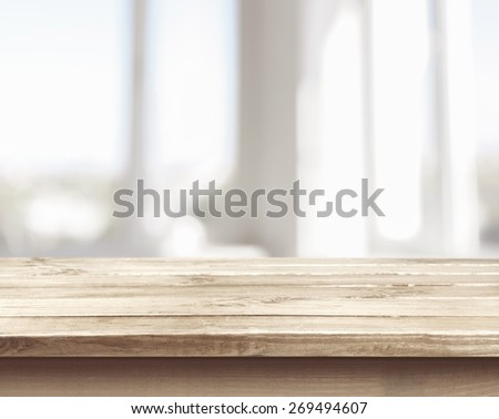 Background. Wooden table on defocuced window with curtain background - stock photo