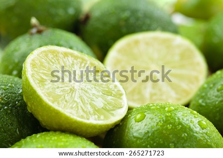 Backgrounds. Close up shot of wet  limes. Focus on the central part of sliced lime. - stock photo