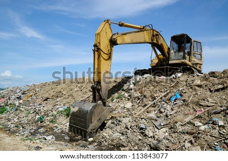 Backhoe at garbage dump with blue sky. - stock photo