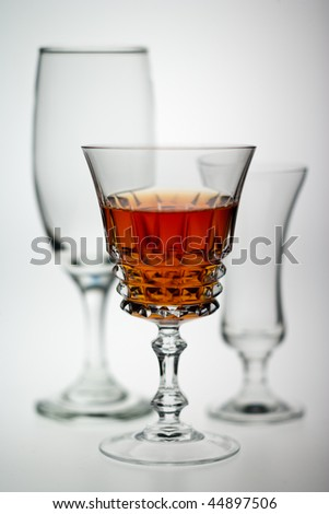 Backlit drinks glasses with orange coloured drink - stock photo