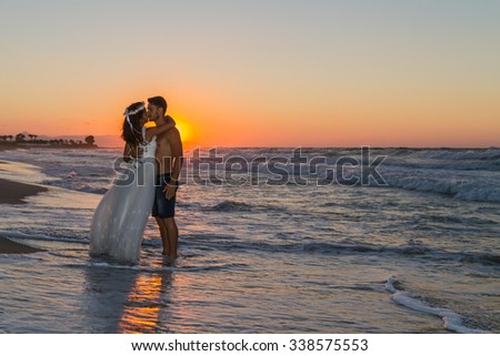 Backlit partially silhouetted newly wed young couple at the beach, enjoying the beautiful hazy sunset, wearing a wedding dress and shorts, barefoot, getting wet, teasing and kissing one another. - stock photo