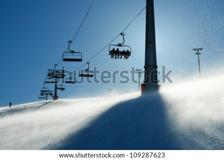 backlit scenes with ski lift chairs on hillside, Levi ski resort, Finland - stock photo