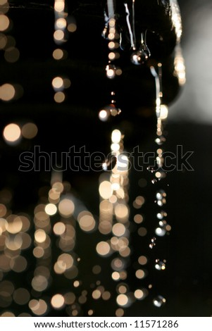 Backlit water drops on dark background - stock photo