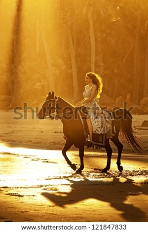 backlit woman on horseback in formal dress riding on beach - stock photo