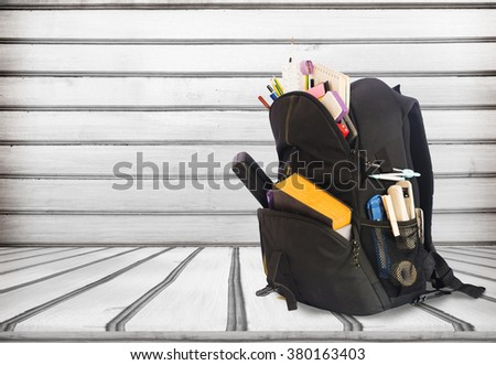 Backpack full of school supplies. Shot on wooden background.schoolbag with supplies for education - stock photo