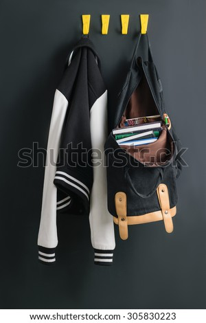Backpack with books weighs on the wall next to the bomber - stock photo
