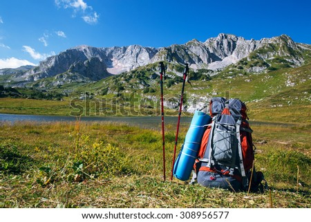 backpack with nordic walking sticks in mountain - stock photo