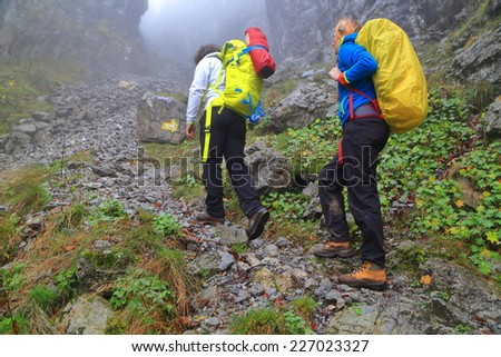 Backpacker ascending a rocky trail in the morning mist - stock photo