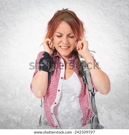 backpacker covering her ears over textured background - stock photo