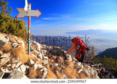 Backpacker descending a rocky mountain trail near trail sign - stock photo