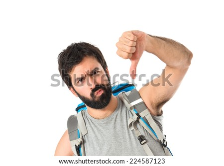 Backpacker doing a bad signal over white background - stock photo