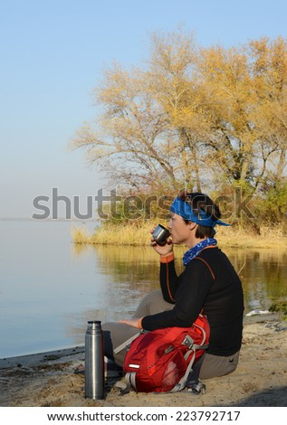 Backpacker drinking tea on the beach  - stock photo