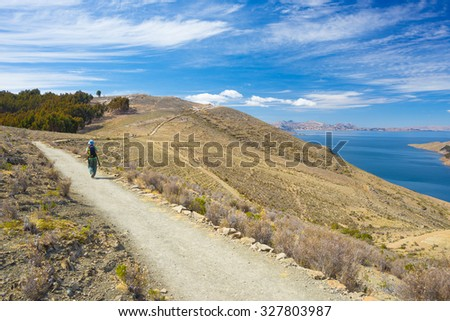 Backpacker exploring the majestic Inca trails on the Island of the Sun, Titicaca Lake, among the most scenic travel destination in Bolivia. Concept of travel adventures and tourism in the Americas. - stock photo