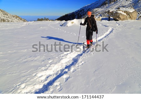 Backpacker in deep snow on the mountain - stock photo