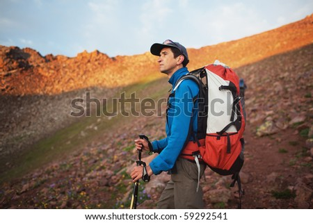 Backpacker in morning mountains awaiting the sunrise - stock photo