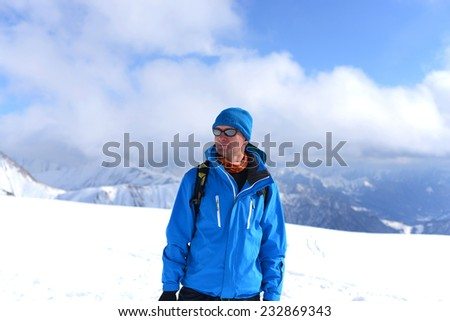 Backpacker in the snowy mountains - stock photo