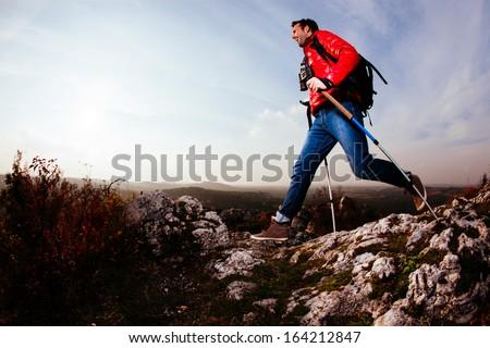 Backpacker jumping on rocks - stock photo