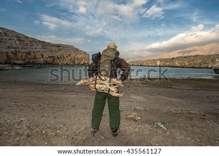 Backpacker on the sandy beach, big backpack loaded with firewood - stock photo