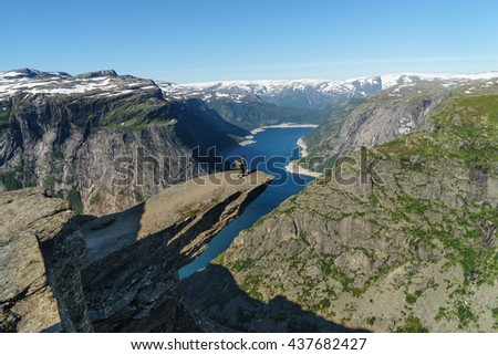 Backpacker on Trolltunga (Devil's tongue), Hordaland, Norway - stock photo