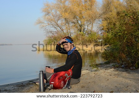 Backpacker resting on the beach  - stock photo