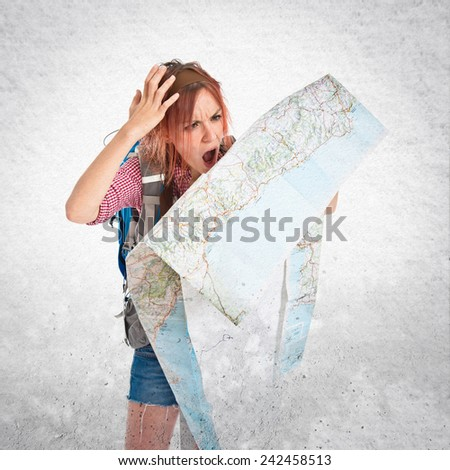 backpacker showing map over textured background - stock photo