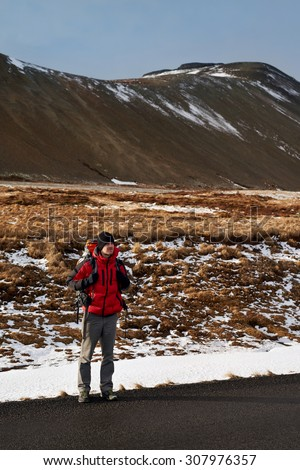 Backpacker travelling holiday on a budget hitchhiking for a ride on empty road, in harsh winter snowy cold extreme conditions - stock photo
