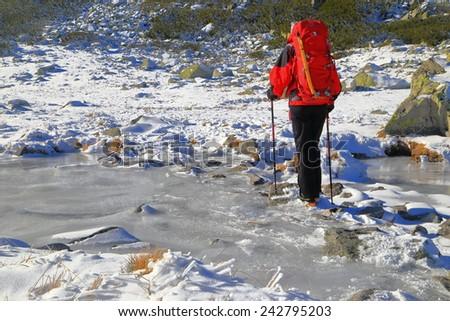 Backpacker walking across small frozen river during winter  - stock photo