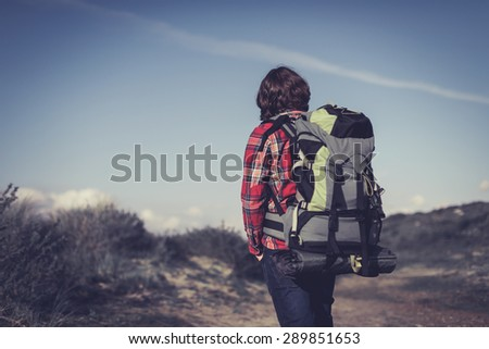 Backpacker wearing a large backpack of camping gear walking through hilly scrub standing facing away from the camera surveying his surroundings - stock photo