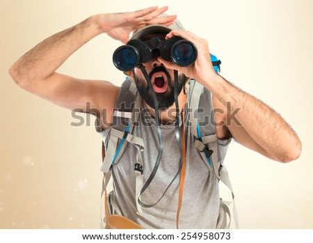 Backpacker with binoculars over isolated white background - stock photo