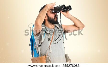 Backpacker with binoculars over ocher background - stock photo
