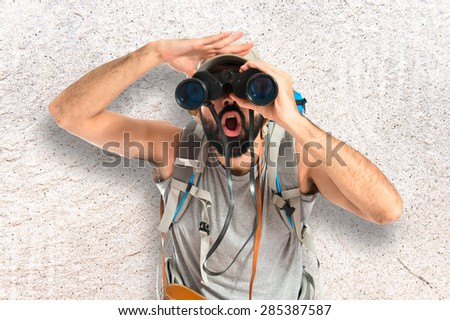 Backpacker with binoculars over textured background - stock photo