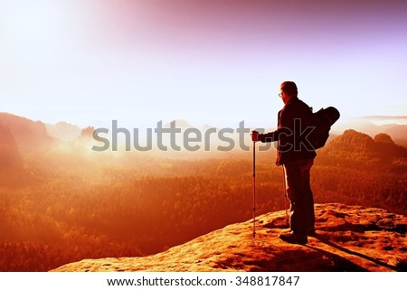 Backpacker with eyeglasses and poles in hand. Sunny spring daybreak in rocky mountains. Hiker with big backpack stand on rocky view point above misty valley. Vivid colors. - stock photo