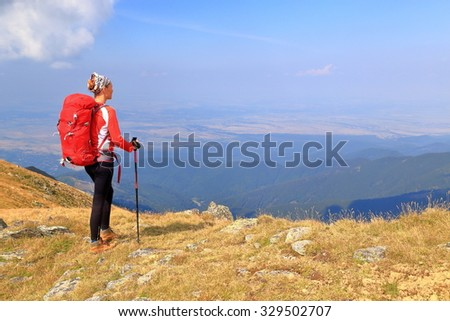 Backpacker woman admires the view from the mountain in fine day - stock photo