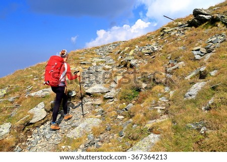 Backpacker woman ascending a rocky trail on the mountain - stock photo